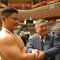 全日本相撲選手権で優勝した谷岡(左)と握手する近大の伊東監督=東京・両国国技館で2019年12月1日午後6時25分、村社拓信撮影