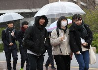 Applicants head to a venue for the National Center Test for University Admissions in Hachioji, western Tokyo, on Jan. 18, 2020, as snow falls over the area. (Mainichi/Junichi Sasaki)