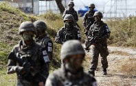 In this Oct. 13, 2015 file photo, South Korean Army soldiers patrol during the demonstration of search operation at a training field near the demilitarized zone (DMZ) in Cheorwon, South Korea. (AP Photo/Lee Jin-man)