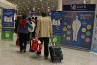 In this Jan. 13, 2020 photo, travelers pass by a health checkpoint before entering immigration at the international airport in Beijing. AP Photo/Ng Han Guan)