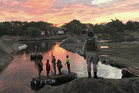 A Mexican National Guard looks at local residents crossing the Suchiate River, near Ciudad Hidalgo, on the Mexican border with Guatemala, on Jan. 17, 2020. (AP Photo/Maria Verza)