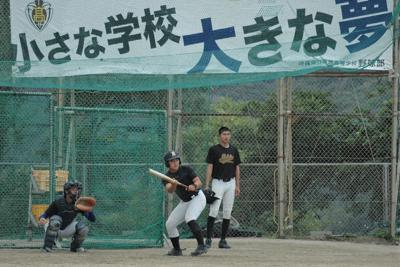 「小さな学校 大きな夢」のスローガンを掲げたグラウンドでバント練習に取り組む本部の選手たち=沖縄県本部町の同校グラウンドで2020年1月9日、吉見裕都撮影