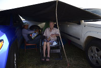 In this Friday, Jan. 10 photo, residents from the Indios neighborhood of Guayanilla, Puerto Rico, Milagros Figueroa and Ruben Fantausi, sit under a tarp between vehicles parked on a private hay farm where locals affected by earthquakes have set up shelter amid aftershocks in Guayanilla, Puerto Rico. (AP Photo/Carlos Giusti)