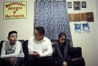 In this Nov. 21, 2019, photo Audencio Lopez, center, who crossed the border illegally as a teenager in 1997, is seated with two of his children, Anaias, 12, left, and Mercy, 8, right, during an interview with The Associated Press, at their home in Lynn, Mass. After going through the immigration court process for seven years, Lopez was told at a court hearing this past fall that the government won't oppose granting him a visa due to his