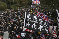 Participants wave British and U.S. flags during a rally demanding electoral democracy and calling for a boycott of the Chinese Communist Party and all businesses seen to support it in Hong Kong, Sunday, Jan. 19, 2020. (AP Photo/Ng Han Guan)