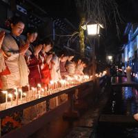 ろうそくに火をともし良縁を願う女性たち=岐阜県飛驒市古川町で