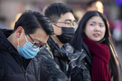 新型コロナウイルスの感染者が初めて確認された北京で、マスクを身につけた旅行客=20日、AP