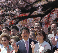 Prime Minister Shinzo Abe, center, and his wife Akie, center right, pose for photos along with guests during a cherry blossom-viewing party at Shinjuku Gyoen National Garden in Tokyo's Shinjuku Ward on April 13, 2019. (Mainichi/Shinnosuke Kyan)