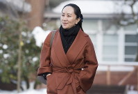 Huawei chief financial officer Meng Wanzhou, who is out on bail and remains under partial house arrest after she was detained last year at the behest of American authorities, leaves her home in Vancouver, British Columbia, on Jan. 17, 2020, as she heads to B.C. Supreme Court for a case management hearing. (Jonathan Hayward/The Canadian Press via AP)