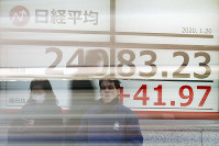 Pedestrian stand in front of an electronic stock board showing Japan's Nikkei 225 index at a securities firm in Tokyo, on Jan. 20, 2020. (AP Photo/Eugene Hoshiko)