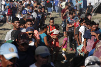 Honduran migrants stand in line for breakfast at a temporary shelter in Tecun Uman, Guatemala in the border with Mexico, on Jan. 19, 2020. AP Photo/Moises Castillo)