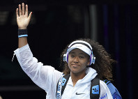 Japan's Naomi Osaka waves as she arrives on Rod Laver Arena for her first round singles match against Marie Bouzkova of the Czech Republic at the Australian Open tennis championship in Melbourne, Australia, on Jan. 20, 2020. (AP Photo/Lee Jin-man)
