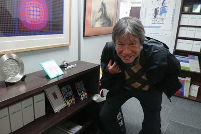 ニコリの鍜治真起社長。書棚には数独の日めくりカレンダーや単行本が並ぶ=東京都中央区で