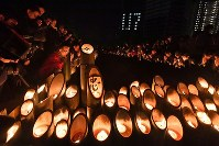 People offer a silent prayer in front of bamboo lanterns for the victims of the 1995 Great Hanshin Earthquake at an annual memorial service at Higashi Yuenchi park in Kobe's Chuo Ward, in western Japan, at the time of the jolt, 5:46 a.m., on Jan. 17, 2020. (Mainichi/Yusuke Komatsu)