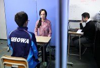A student, front left, is seen in a mock interview with a humanoid at Showa Gakuen, a school for children with developmental disabilities, in Tokyo's Nakano Ward, on Dec, 26, 2019. A school staffer to the right, separated from the student with a partition, controls the interview questions and has the humanoid speak on his behalf. (Mainichi/Yuki Miyatake)