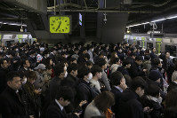 Commuters form multiple lines on a platform for a train during evening rush hours at Shinagawa Station in Tokyo, on Jan. 14, 2020. (AP Photo/Jae C. Hong)