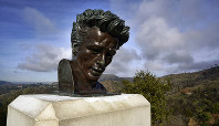 In this Jan. 17, 2020, photo, the Hollywood hills are seen behind a bust of actor James Dean at the Griffith Observatory in Los Angeles. (AP Photo/Richard Vogel)