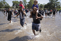 Central American migrants carry children as they run across the Suchiate River from Guatemala to Mexico, near Ciudad Hidalgo, Mexico, on Jan. 20, 2020. (AP Photo/Santiago Billy)
