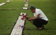 A woman places flowers on the grave of a person who died during the 1989 U.S. military invasion that ousted Panamanian strongman Manuel Noriega, on the 30th anniversary of the invasion in Panama City, on Dec. 20, 2019. (AP Photo/Arnulfo Franco)