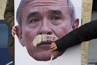 In this Dec. 13, 2019 photo, a protester plucks a false mustache from a picture of U.S. Ambassador to South Korea Harry Harris during a rally to denounce the United States' policies against North Korea, near the U.S. embassy in Seoul, South Korea. (Lee Yong-hwan/Newsis via AP)