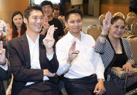 Thailand's Future Forward Party leader Thanathorn Juangroongruangkit, left, poses for media with party members at the headquarters in Bangkok, Thailand, on Jan. 21, 2020. (AP Photo/Sakchai Lalit)