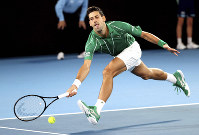 Serbia's Novak Djokovic reaches for a forehand return to Germany's Jan-Lennard Struff during their first-round singles match the Australian Open tennis championship in Melbourne, Australia, on Jan. 20, 2020. (AP Photo/Lee Jin-man)