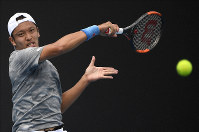 Japan's Tatsuma Ito makes a forehand return to India's Prajnesh Gunneswaran during their first-round singles match at the Australian Open tennis championship in Melbourne, Australia, on Jan. 21, 2020. (AP Photo/Andy Brownbill)
