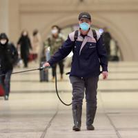 駅で消毒剤をまく職員=中国湖北省武漢市で22日、AP (Chinatopix via AP)