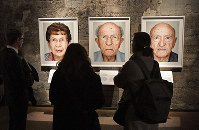 Visitors look at portrait photos of the exhibition 'Survivors - Faces of Life after the Holocaust' at the former coal mine Zollverein in Essen, Germany, on Jan. 21, 2020. (AP Photo/Martin Meissner)