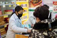 Staff sell masks at a Yifeng Pharmacy in Wuhan, China, Jan. 22, 2020. (AP Photo/Dake Kang)