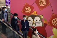 People wear face masks as they ride an escalator at the Hong Kong International Airport in Hong Kong, on Jan. 21, 2020. (AP Photo/Ng Han Guan)