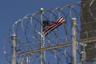 In this April 17, 2019 file photo reviewed by U.S. military officials, a U.S. flag flies inside the razor wire of the Camp VI detention facility, April 17, 2019, in Guantanamo Bay Naval Base, Cuba. (AP Photo/Alex Brandon)