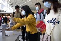 Travelers wearing face masks are seen at Hong Kong International Airport in Hong Kong, on Jan. 21, 2020. (AP Photo/Ng Han Guan)
