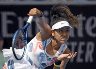 Japan's Naomi Osaka serves to China's Zheng Saisai during their second-round singles match at the Australian Open tennis championship in Melbourne, Australia, on Jan. 22, 2020. (AP Photo/Andy Brownbill)