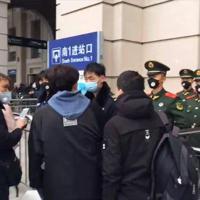 封鎖される直前、武漢の漢口駅近くで旅行者らをチェックする当局の職員ら(ビデオ画像から)=23日、AP