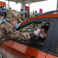 高速道路の料金所で、デジタル体温計を使い運転手の体温を測る民兵=中国湖北省武漢で1月23日、AP