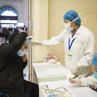 中国湖北省武漢市の漢口駅で、乗客の体温を測る医療関係者=2020年1月22日、新華社AP