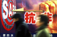 In this Dec. 18, 2003, file photo, people walk past a local government's anti-SARS advertisement in Shanghai, China. Chinese characters on the advertisement says
