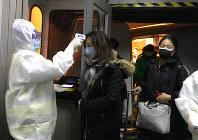 Health Officials in hazmat suits check body temperatures of passengers arriving from the city of Wuhan on Jan. 22, 2020, at the airport in Beijing, China. (AP Photo Emily Wang)