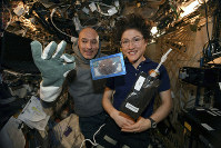 In this photo made available by U.S. astronaut Christina Koch via Twitter on Dec. 26, 2019, she and Italian astronaut Luca Parmitano pose for a photo with a cookie baked on the International Space Station. (NASA via AP)