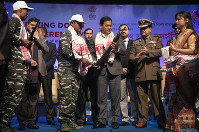 Assam Chief minister Sarbananda Sonowal, third from right, receives arms from one of the rebels who surrendered during a ceremony in Gauhati, India, on Jan. 23, 2020. (AP Photo/Anupam Nath)
