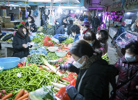 In this photo released by China's Xinhua News Agency, people shop for vegetables at a market in Wuhan in central China's Hubei Province, on Jan. 23, 2020. (Xiao Yijiu/Xinhua via AP)