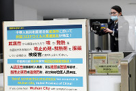 A quarantine officer sets up an extra thermography camera to monitor travelers from China's Wuhan and other cities at Narita International Airport in Narita, near Tokyo, on Jan. 23, 2020. (AP Photo/Eugene Hoshiko)