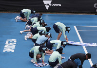 Ball kids dry off a court after rain halted play at the Australian Open tennis championship in Melbourne, Australia, on Jan. 23, 2020. (AP Photo/Lee Jin-man)