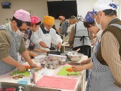 高齢の男性に栄養バランスのよい料理を教える女子学生たち