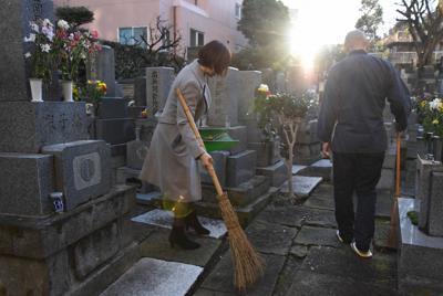 朝日の差し込むなか、境内を掃除する=東京都港区で筆者撮影