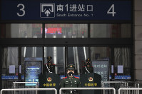 In this Jan. 23, 2020 photo, Chinese paramilitary police stand guard outside the closed Hankou Railway Station in Wuhan in central China's Hubei Province. (Chinatopix via AP)