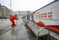 A worker hoses down benches outside the closed Hankou Railway Station in Wuhan in central China's Hubei Province, on Jan. 23, 2020. (Chinatopix via AP)