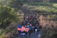 Central American migrants walk carrying a handmade U.S. flag and banners, after crossing the Suchiate River from Guatemala in Ciudad Hidalgo, Mexico, on Jan. 23, 2020. (AP Photo/Marco Ugarte)