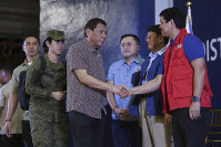 In this Jan. 23, 2020 photo provided by the Malacanang Presidential Photographers Division, Philippine President Rodrigo Duterte, center, is greeted by Social Welfare and Development Secretary Rolando Bautista, right, at the San Isidro Central School during the distribution of benefits to former rebels in Leyte province, southern Philippines. (Karl Norman Alonzo/Malacanang Presidential Photographers Division via AP)